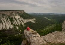 Турист фотографируется на фоне пейзажей города крепости Чуфут - Кале. Бахчисарайский район, город-крепость Чуфут-Кале